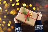 Childers Hands Hold A Present Box. Gift Wrapped In Kraft Paper And Decorated With A Spruce Branch An poster