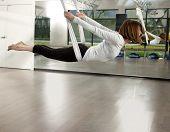 image of gravity  - Woman doing anti gravity yoga exercise in fitness center - JPG