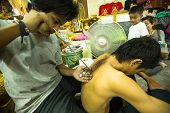NAKHON CHAI, THAILAND - MAR 1: Unidentified master makes traditional Yantra tattooing on Mar 1, 2012