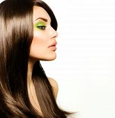 Hair. Beautiful Brunette Girl. Healthy Long Brown Hair. Beauty Model Woman with Green makeup. Trendy