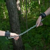 stock photo of sado-masochism  - Women Hands Chained on Forest Green Background - JPG