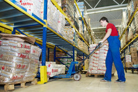 foto of food truck  - worker with fork pallet truck stacker in warehouse loading Group of food packages - JPG