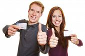 Young man and happy woman with drivers licence holding their thumbs up