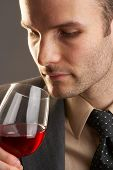 pic of red wine  - man taking a smell at a glass of red wine - JPG