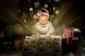 image of solemn  - one-year-old little girl solemnize Christmas sit under Christmas-tree and reach gift of box horizontal photo