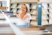 pic of librarian  - Mature female librarian working in library - JPG