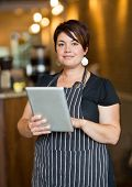 Portrait of female owner holding digital tablet while standing in cafeteria