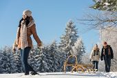 pic of luge  - Sunny winter day woman pulling sledge couple walking in snow - JPG