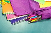 stock photo of knapsack  - Purple backpack with school supplies on green desk background - JPG