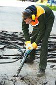 image of hammer drill  - Builder worker with pneumatic jack hammer drill equipment breaking asphalt at construction road works - JPG