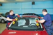 stock photo of auto garage  - Automobile glaziers workers replacing windscreen or windshield of a car in auto service station garage - JPG