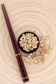 stock photo of ginseng  - Ginseng root herb with chopsticks on a circular wooden bowl - JPG