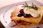 stock photo of french toast  - Delicious french toast with bacon syrup berries and cream on a white plate on a wooden table - JPG