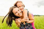 stock photo of hug  - Mother and child are hugging and having fun outdoor in nature - JPG