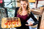 stock photo of confectioners  - Female confectioner presenting tray of cake in bakery or pastry shop - JPG