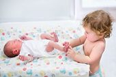 stock photo of diaper change  - Portrait Of A Cute Curly Toddler Girl Playing With The Feet Of Her Newborn Baby Brother - JPG