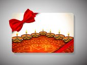 stock photo of diwali lamp  - Diwali festival gift card with illuminated lit lamps on floral decorated floor with ribbon bow - JPG