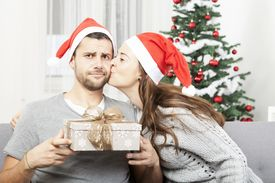 stock photo of queer  - man is skeptical about christmas gift while his girlfriend gives him a kiss [[** Note: Shallow depth of field ** Note: Soft Focus at 100%, best at smaller sizes - JPG
