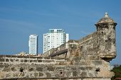 stock photo of fortified wall  - Modern apartment block towering above the fortified walls of the historic Spanish colonial city of Cartagena de Indias in Colombia - JPG