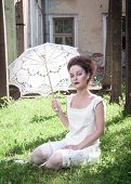 stock photo of gothic girl  - Beautiful young gothic girl in white shirt with umbrella outdoor - JPG