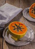 image of papaya  - sliced papaya on a vintage pewter plates with spoon - JPG