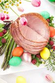 stock photo of ester  - Whole baked honey sliced ham with fresh raspberry asparagus dyed Ester eggs Easter cake and cross buns - JPG