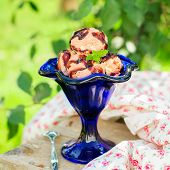 foto of chocolate fudge  - Chocolate Ice Cream with Fudge Sauce in a Blue Bowl on a Sunny Summer Day square copy space for your text - JPG