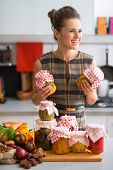 foto of pickled vegetables  - Happy young housewife with jars of pickled vegetables - JPG