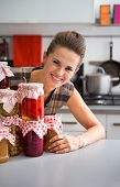 picture of pickled vegetables  - Portrait of happy young housewife looking out from jars with homemade fruits jam and pickled vegetables - JPG