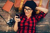 picture of lie  - Top view of beautiful young woman in headwear lying on the floor holding mobile phone and smiling - JPG