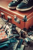 foto of old suitcase  - Old travel suitcase sneakers clothing map filmstrip and retro film camera - JPG