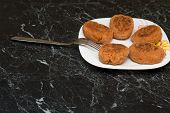 picture of pork cutlet  - cutlet and a fork on white plate on marble table. Photo ** Note: Shallow depth of field - JPG