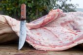 image of slaughter  - Slaughterer knife and pieces of pig over wooden trough - JPG