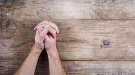 image of hand god  - Hands of praying young man on a wooden desk background - JPG