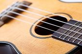 picture of musical instrument string  - Small Hawaiian four stringed ukulele guitar body closeup. Musical instruments shop or learning school concept ** Note: Shallow depth of field - JPG
