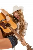 foto of cowgirl  - Sesy cowgirl in cowboy hat with a nylon string acoustic guitar - JPG