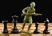 stock photo of battle  - Chessmen with green toy soldier taking on to battle - JPG