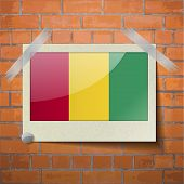 picture of guinea  - Flags of Guinea scotch taped to a red brick wall - JPG