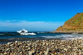 picture of atlantic ocean  - Wild stone beach and mountain on coast or shore of the Atlantic ocean with waves and sky with clouds and skyline or horizon in Tenerife Canary island Spain at spring or summer - JPG