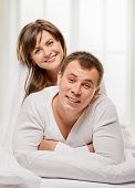 picture of laying-in-bed  - Happy smiling couple laying laughing in bed with light window background - JPG