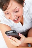 image of sms  - Young woman lying in bed and talking on the phone or reading sms isolated on white background - JPG