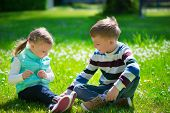 picture of brother sister  - Happy little brother and sister playing on grass in park - JPG