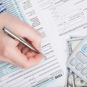 stock photo of cpa  - Taxpayer filling out USA 1040 Tax Form  - JPG