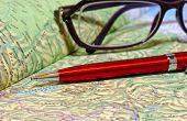 foto of atlas  - Ballpoint pen and glasses lie on geographical atlas - JPG
