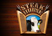 foto of cow head  - Wooden wall with an open window with a head of cow text Steak house and two steel forks - JPG