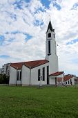 image of church  - Modern built white church with red roof photographed on a cloudy summer day - JPG
