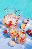 stock photo of jug  - Ice cold homemade strawberry lemonade in jug and glasses with paper straws on outdoor summer pool side table - JPG