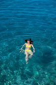 pic of top-hat  - Young woman in yellow swimsuit and big hat swimming and relaxing in the blue water sea - JPG