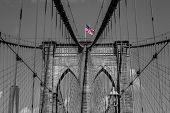 image of brooklyn bridge  - A view of the arches of Brooklyn Bridge in NYC with the bridge sky and city in black and white but the USA flag in color - JPG