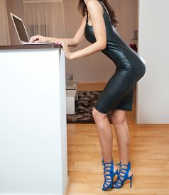 picture of tight dress  - Perfect body woman in short tight fit leather dress and blue shoes posing relaxed in a modern kitchen - JPG